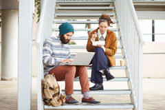 Hipster couple using computer and eating lunch outdoors Stock Photography
