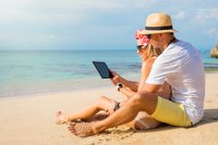 Couple using tablet on the beach Stock Images