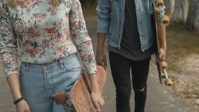 Hipster Couple Walks with Skateboards stock footage