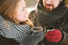 Hipster couple in winter park with hot tea from thermos Royalty Free Stock Photos