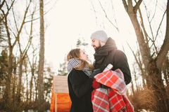 Hipster couple in winter park with hot tea thermos Stock Image