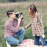 Hipster couple. Young hipster guy photographs the girl on a vintage camera Royalty Free Stock Photography