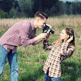 Hipster couple. Young hipster guy photographs the girl on a vintage camera Royalty Free Stock Photo
