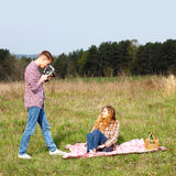 Hipster couple. Young hipster guy photographs the girl on a vintage camera Royalty Free Stock Image