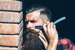 Hipster cutting with razor Royalty Free Stock Images