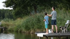 Hipster dad and boy enjoying fishing at the pond stock video footage
