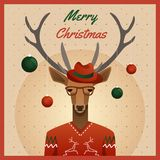 Hipster deer with hat and christmas balls Royalty Free Stock Photos