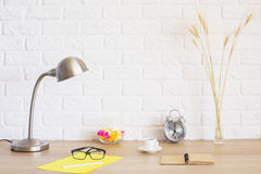 Hipster desktop. Creative desktop with glasses, coffee cup, lamp, stationery and other items on white brick wall background Stock Photos
