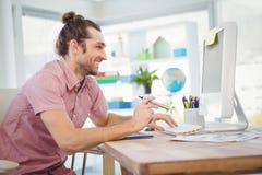 Hipster die terwijl het houden van elektronische sigaret glimlachen Stock Foto's