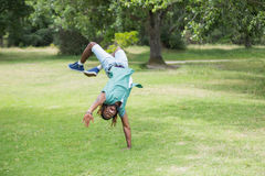 Hipster doing back flip in the park Stock Photos