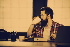 Hipster drinking coffee at desk. In creative office stock photo