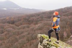 Hipster - een klimmer in een benedenjasje en een gebreide GLB-tribune en rust op de bovenkant van een rots royalty-vrije stock foto's