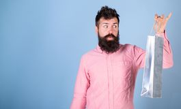 Hipster on excited face shopping addicted or shopaholic. Guy shopping on sales season with discounts. Sale and discount. Concept. Man with beard look at stock image