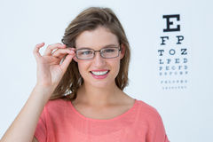 Hipster with eyeglasses and eyes test behind her Royalty Free Stock Images