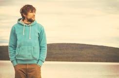 Hipster för ung man som står ensamt utomhus- arkivbild