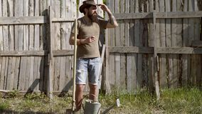 Hipster farmer relaxing at nature background. Full body portrait of bearded man farmer with shovel having fun in a farm stock footage