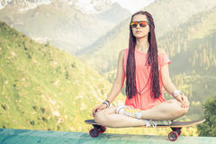 Hipster fashion girl doing yoga, relaxing on skateboard at mountain. Closeup image of Hipster fashion girl doing yoga, relaxing and sitting on skateboard at Royalty Free Stock Photos
