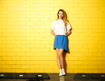 Hipster Fashion Girl at the Yellow Wall Royalty Free Stock Photos