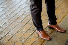Hipster fashion man`s legs in black jeans and brown leather. Boots on wooden floor royalty free stock photos