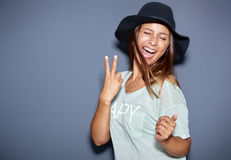 Hipster fashionable young woman giving a V-sign Stock Photos