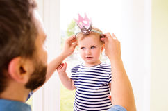 Hipster father with daughter putting crown on her head Royalty Free Stock Photos