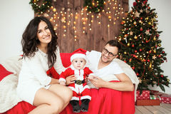 Hipster father and mother holding baby in santa suit Stock Photography