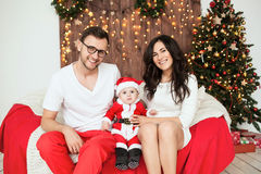 Hipster father and mother holding baby in santa suit Stock Image