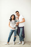 Hipster father, mother holding cute baby boy over white backgrou Royalty Free Stock Photos
