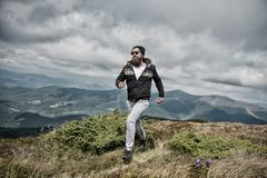 Hipster feels free while hiking, sky background. Hipster or brutal macho conquers mountain. Man with brutal appearance. Hiking. Freedom concept. Man with beard Royalty Free Stock Images