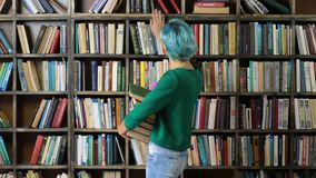 Female student choosing book on shelf in library stock video