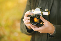 Hipster female photographer shooting outdoors Royalty Free Stock Image