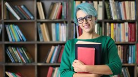 Smiling female student holding books and smiling stock footage