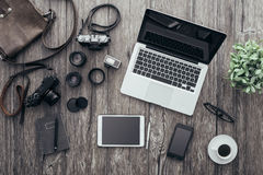 Hipster freelance photographer. Hipster freelance photographic equipment on a wooden desktop with laptop and digital tablet, top view Royalty Free Stock Photo