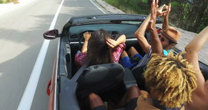 Hipster friends having fun riding in cabriolet. Young hipster friends having fun riding in cabriolet stock video