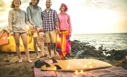 Hipster friends having fun walking with led neon lanterns at beach camping party - Friendship travel concept with young wanderer stock photo