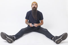 Hipster with a game controller on the floor. Hipster guy with long beard wearing a beanie is holding a video game controller and looking baffled while sitting on Royalty Free Stock Images