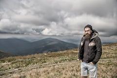 Hipster, gebaarde mens op bergbovenkant op natuurlijke bewolkte hemel royalty-vrije stock foto's