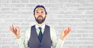 Hipster gesturing while looking up against wall Royalty Free Stock Images