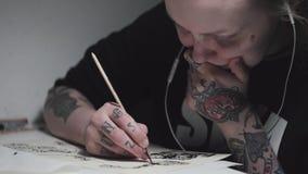 Hipster getatoeeerde kunstenaars punkvrouw die bij bureau in lamplicht schetsen stock video