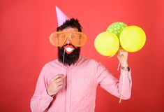 Hipster in giant sunglasses celebrating. Guy in party hat with air balloons celebrates. Man with beard on cheerful face