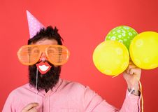 Hipster in giant sunglasses celebrating. Guy in party hat with air balloons celebrates. Photo booth fun concept. Man. With beard on cheerful face holds smiling stock images