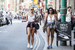 Hipster gilrs dressed in cool Londoner style walking in Brick lane, a street popular among young trendy people Stock Photo