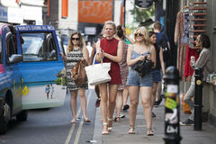 Hipster gilrs dressed in cool Londoner style walking in Brick lane, a street popular among young trendy people Royalty Free Stock Photos