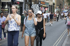 Hipster gilrs dressed in cool Londoner style walking in Brick lane, a street popular among young trendy people Royalty Free Stock Image