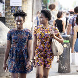 Hipster gilrs dressed in cool Londoner style walking in Brick lane, a street popular among young trendy people Stock Image