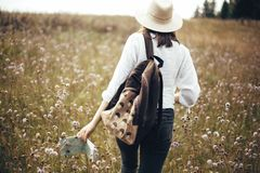 Hipster girl with backpack and map traveling in sunny mountains, walking in  wildflower meadow. Stylish happy woman in hat royalty free stock image