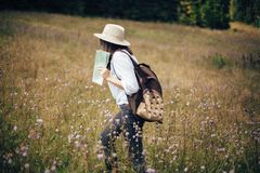 Hipster girl with backpack and map traveling in sunny mountains, walking in  wildflower meadow. Stylish happy woman in hat royalty free stock photography