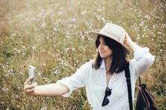 Hipster girl with backpack taking selfie on phone while relaxing in wildflower meadow, traveling in sunny mountains. Stylish woman royalty free stock image