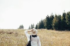 Hipster girl with backpack traveling in sunny mountains, walking in sunny wildflower meadow. Stylish woman in hat exploring and royalty free stock image