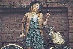Hipster girl with bike and phone. City lifestyle stylish hipster girl with bike using a phone texting on smartphone app in a street
